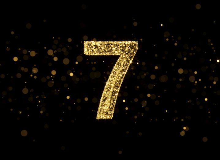 A number seven made of golden glitter on a black, sparkling background.