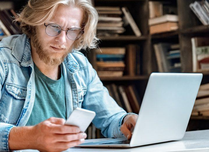 Man with a perplexed face looking at his phone and laptop screen against a bookshelf background.