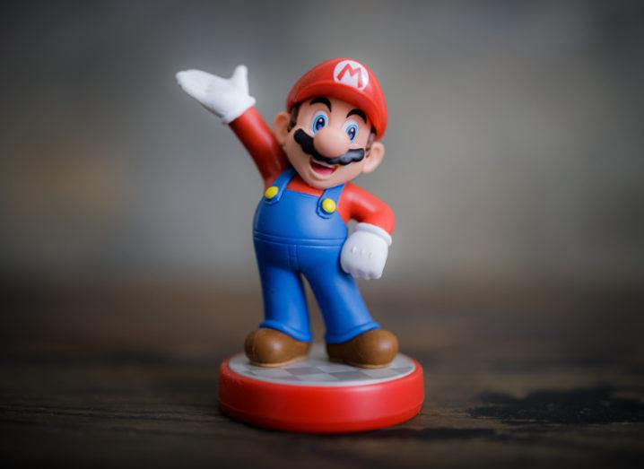 A Super Mario figurine stands with one arm on his hip and the other thrust into the air.