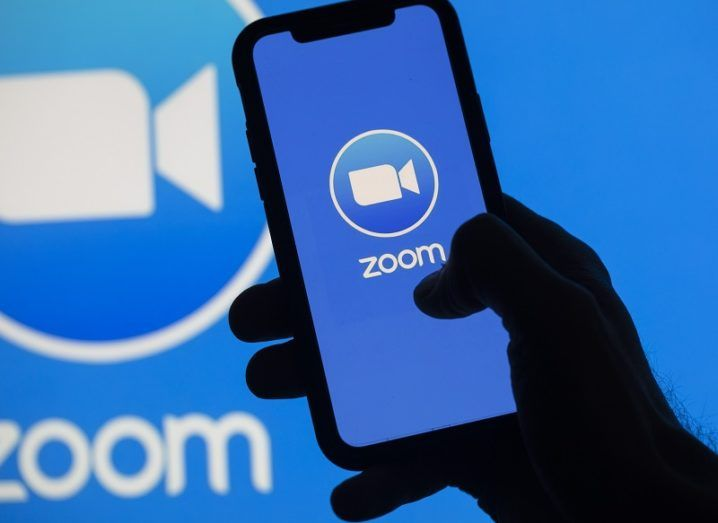 The Zoom logo on a phone in front of a larger Zoom logo on a wall.