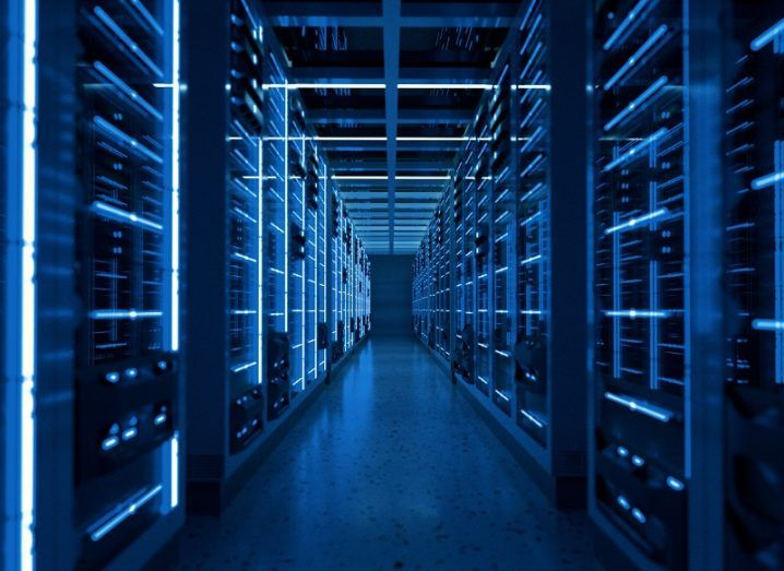 Server racks in a dimly lit server room with a blue hue.
