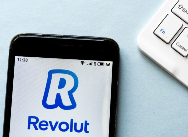 Revolut logo displayed on a smartphone beside the corner of a white keyboard against a pale blue background.