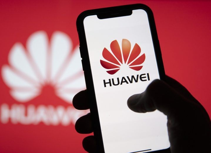Hand holding a phone with the Huawei logo on it in front of a red wall with a white Huawei logo.