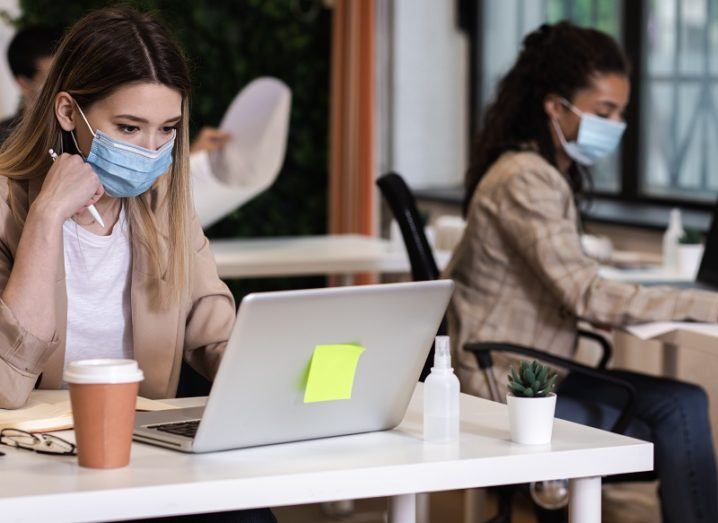 Two women wearing face masks sitting at laptops in a start-up hub.