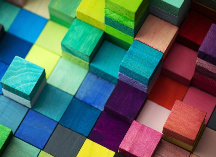 Wooden blocks in many different colours are stacked together.