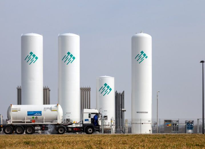 A truck transporting hydrogen fuel driving past large, white tanks filled with hydrogen fuel.