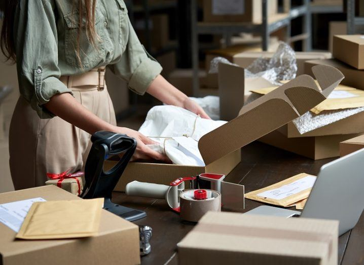 Small business owner packing goods for online shipping beside a laptop.