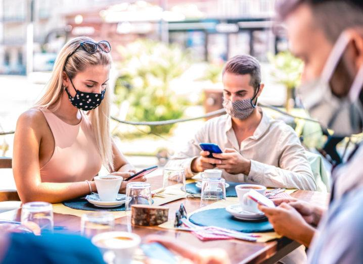 A group of friends seated outdoors and wearing face masks, all using their smartphones.