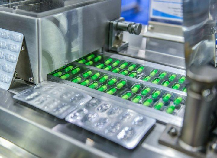 Green tablets on a conveyor belt in a manufacturing facility.