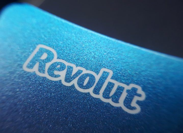 Close-up of a Revolut logo on a blue debit card.