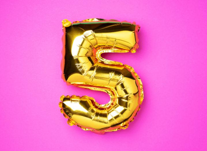 A gold foil balloon shaped like the number five picture on a hot pink background.