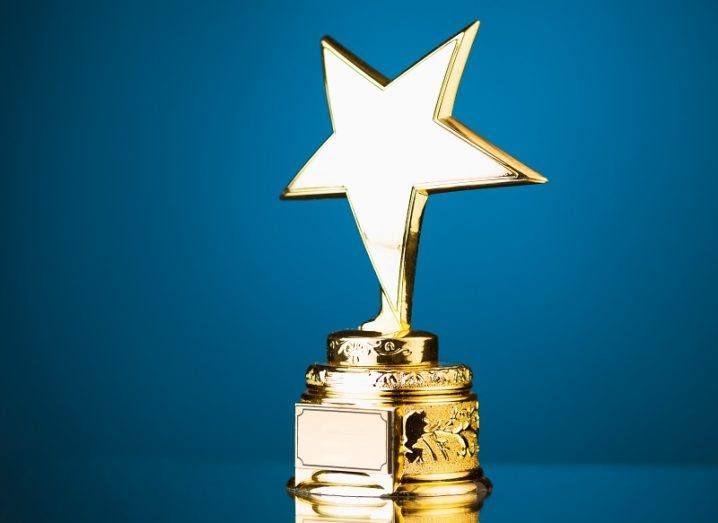 Trophy with a large gold star against a blue background.