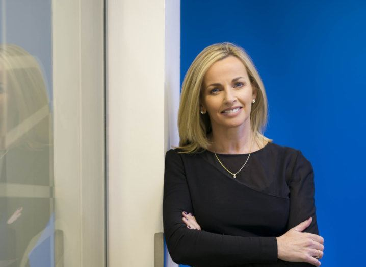 Annette Hickey of PayPal is standing in a bright office with her arms folded.
