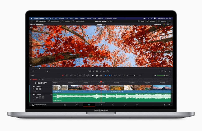 An open MacBook Pro showing video editing software on the screen.