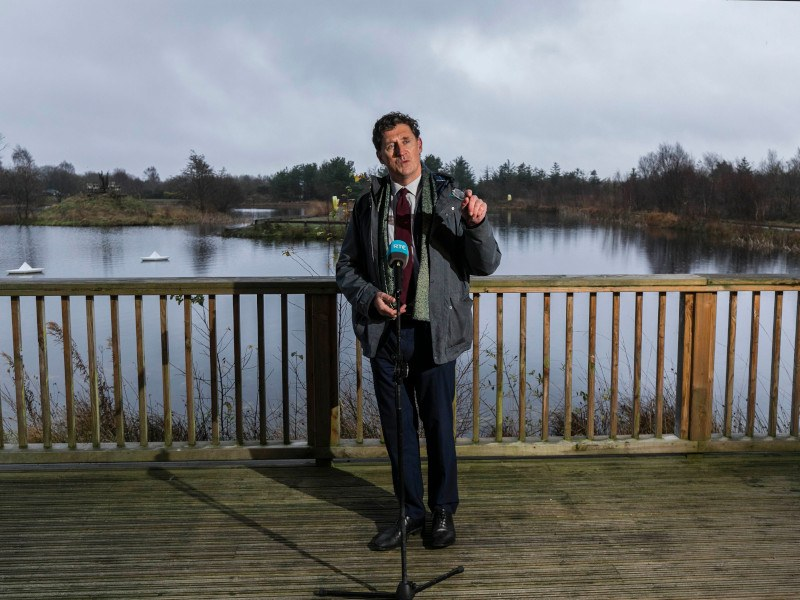 Eamon Ryan stands on a wooden deck beside a bog, speaking into a microphone.