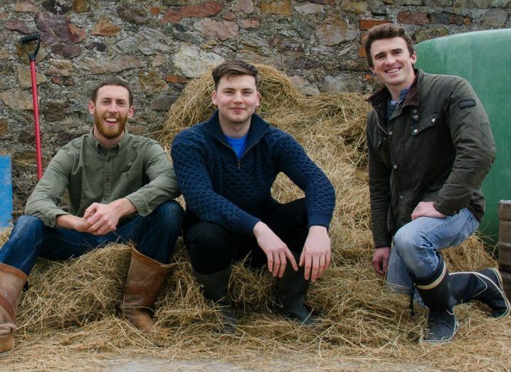 Ryan Scott, Roman Grogan and Sam O'Byrne smiling and sitting on bales of hay.