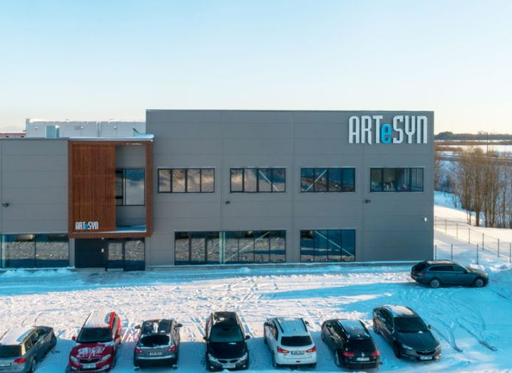 A large grey building with the Artesyn logo pictured on a winter's day with snow covering the surrounding area.