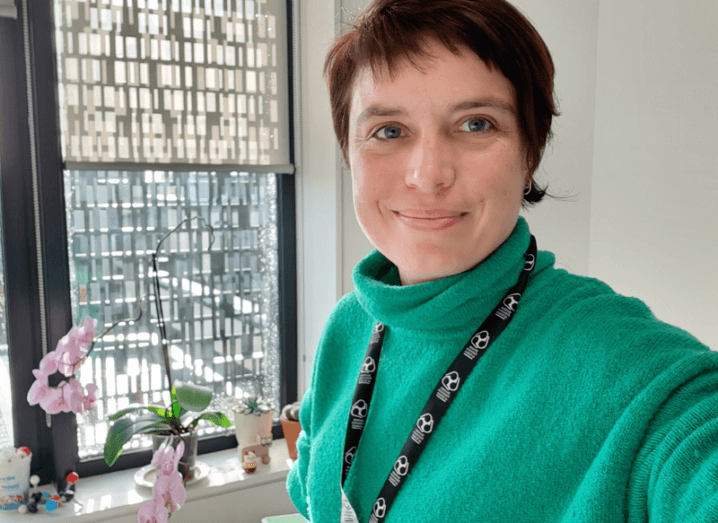 Dr Elisa Fadda in a green jumper smiling and taking a selfie against a windowed background.