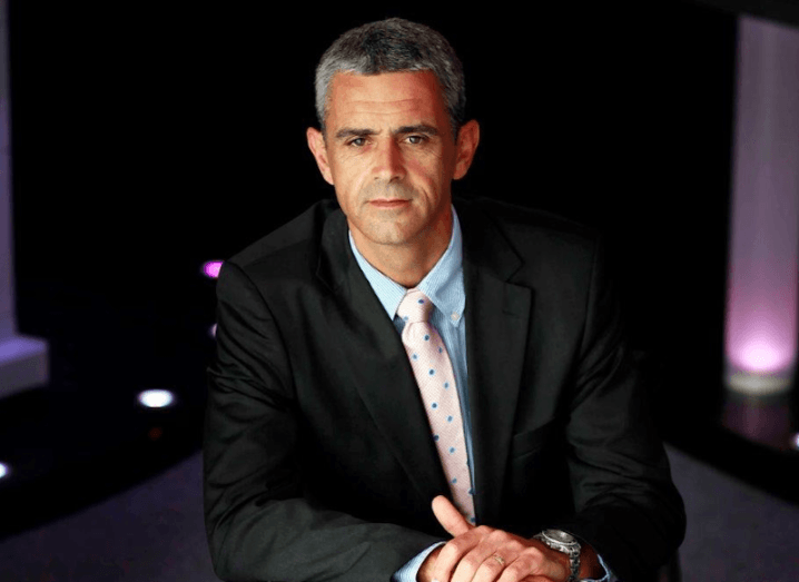Professional shot of Gary Tierney sitting in a suit against a dark background.