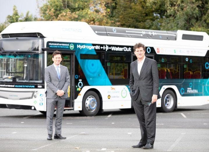Steve Tormey and Eamon Ryan standing in front of the hydrogen bus coloured white and blue.