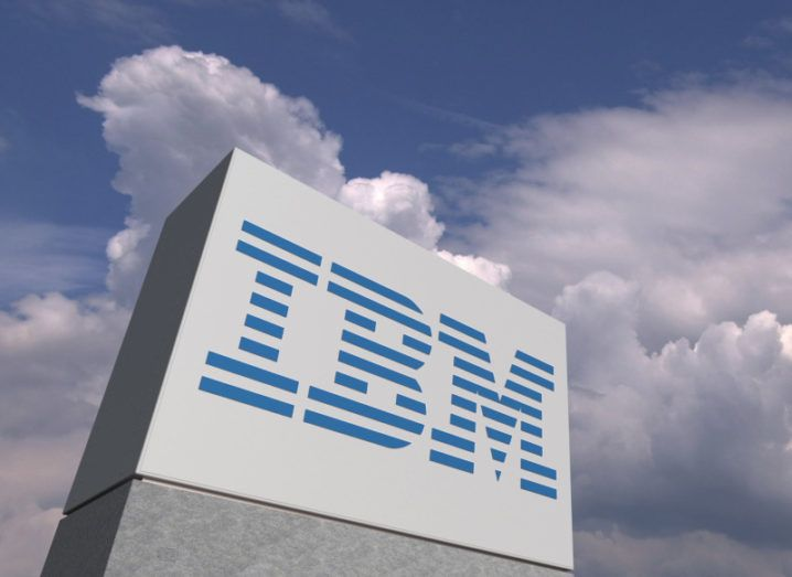 A low-angle shot of a large white block structure with the blue IBM logo on it against a blue, cloudy sky.
