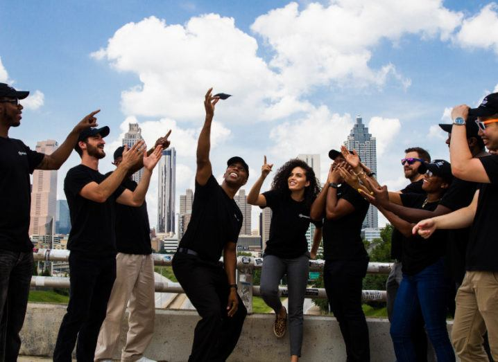A group of people dressed in black point excitedly up to a small black square device held by a man in the centre of the picture. They are standing on a roof in front of a city and a blue sky.