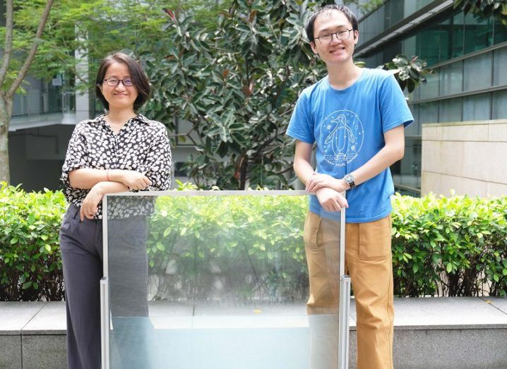 Dr Long Yi and Wang Shancheng smiling and posing with the 'liquid window' against a greenery background.