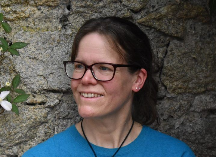 Iris Möller in a blue T-shirt and glasses smiling in front of a stone wall.