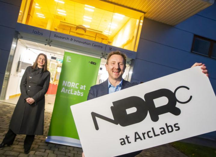 A man and a woman stand outside a building. The man, Liam Dunne, is holding a sign that reads 'NDRC at ArcLabs'.