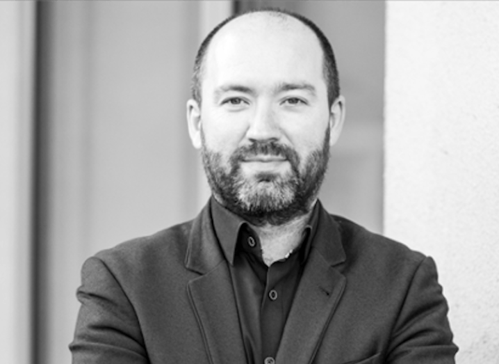Black and white image of a bearded man in a dark shirt and blazer, looking directly at the camera.
