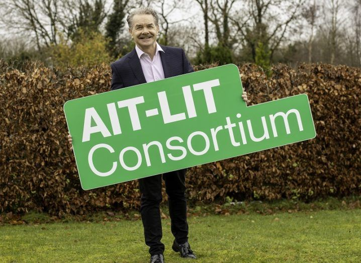 Prof Ciaran O'Cathain smiling in a suit, holding a green sign that says AIT-LIT Consortium.