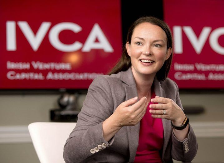 Sarah-Jane Larkin smiling at a desk in front of the IVCA logo.