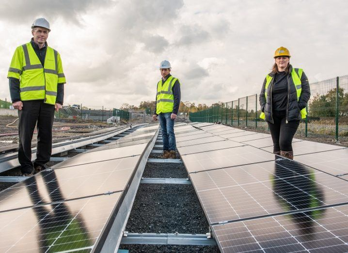 Kieran McKenna, Alan Jackson and Sarah Fogarty in high-vis jackets standing beside a solar array against a cloudy background.