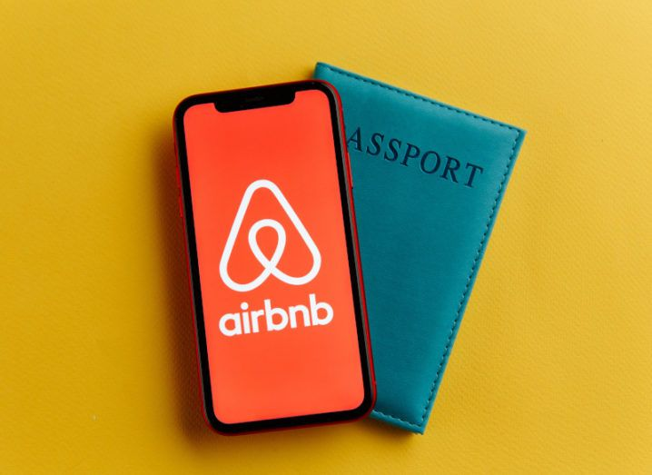 A black smartphone with a full-screen picture of the Airbnb logo on it. The phone sits on top of a dark green passport against a yellow background.