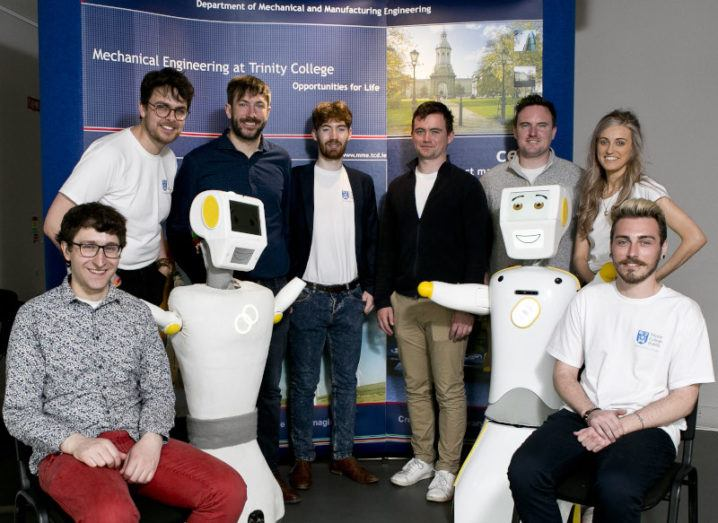 A team of seven men and one woman pose alongside two anthropomorphic white robots with smiling digital faces.