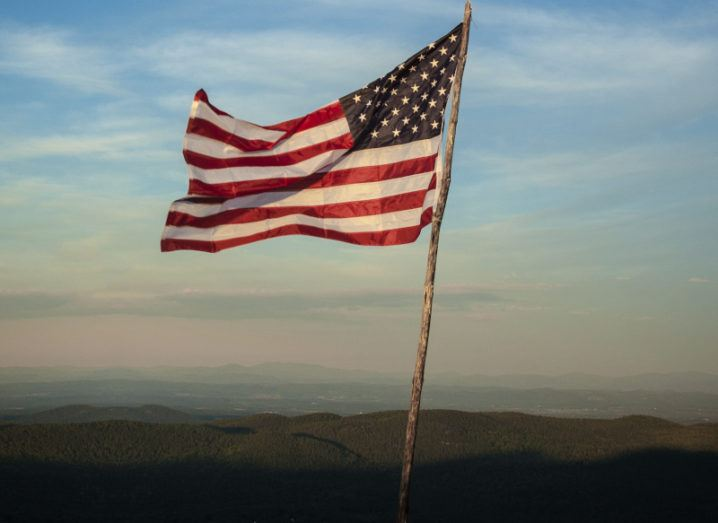 A US flag blowing to the left in the breeze on a hill against a blue cloudy sky that fades to dusty pink.