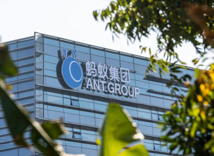 A shot through some greenery of the Ant Group logo on top of an office building against a blue sky.