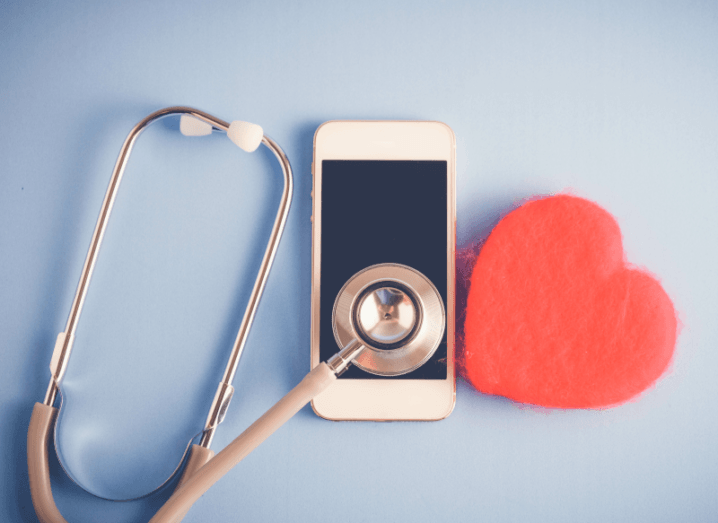 A stethoscope, a phone, and a small felt heart are sitting against a blue background.