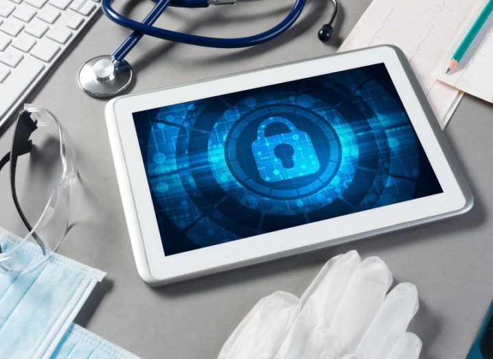 An iPad with a blue padlock icon on the screen sits on a wooden table alongside a stethoscope, medical gloves, masks and protective eyewear.