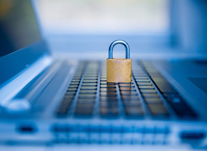 A small gold padlock sits on top of a laptop keyboard, symbolising encryption. The entire picture has a soft blue hue to it.