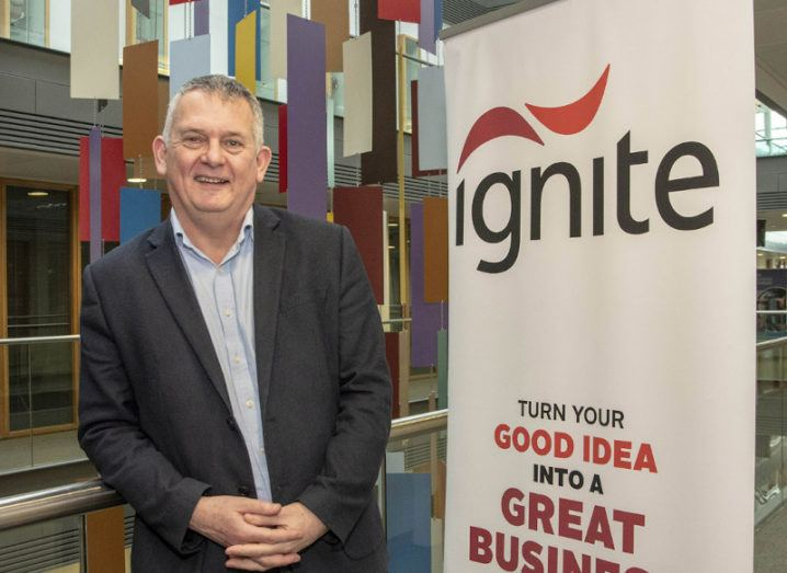 Eamon Curtin stands in a suit beside a sign for the Ignite incubator.