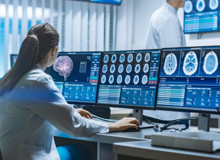 A woman in a lab coat sits at a desk facing three screens, all showing various medical information and brain scans.