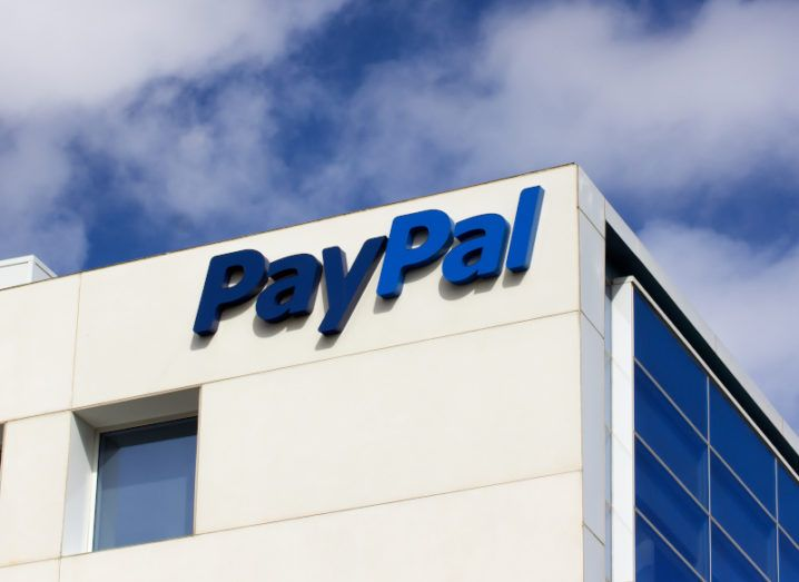 The two-tone blue PayPal logo on the corner of a tall, cream office building against a blue sky with clouds.