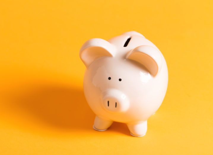 A pale pink piggy bank sits on a bright, mustard-coloured background.