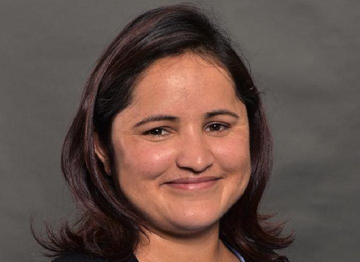 Headshot of Dr Sita Karki smiling against a grey background.