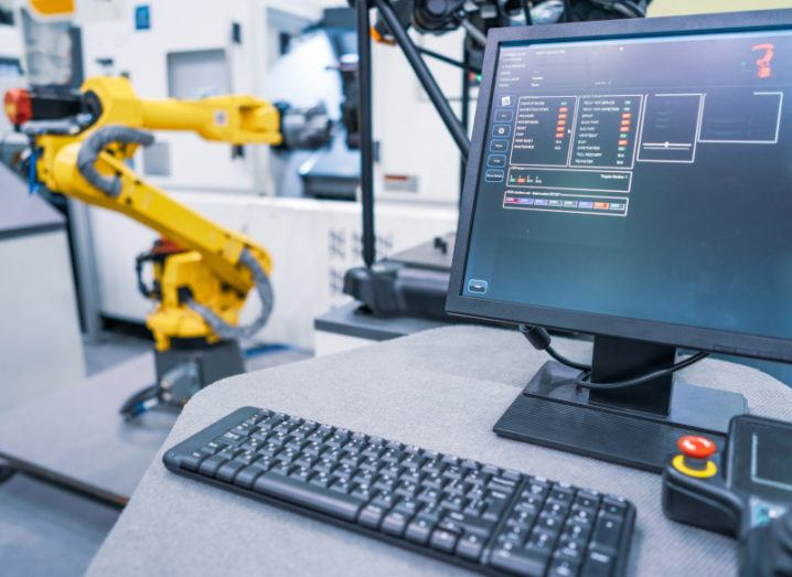 A computer screen in the foreground of a factory, with a yellow robotic arm in the background representing smart manufacturing.