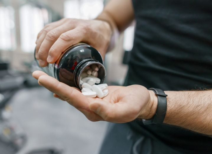 A close-up shot of a man pouring supplements from an orange bottle into his hand. Behind him is some out-of-focus gym equipment.
