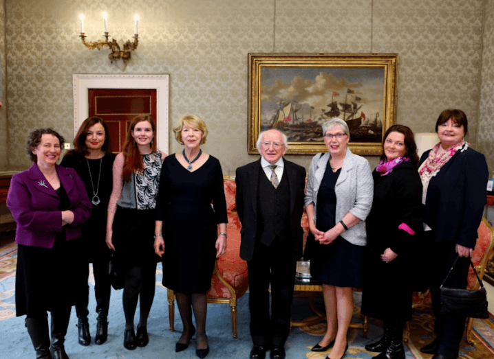A group of four women and a group of three women stand either side of President of Ireland, Michael D Higgins at Áras an Uachtaráin.