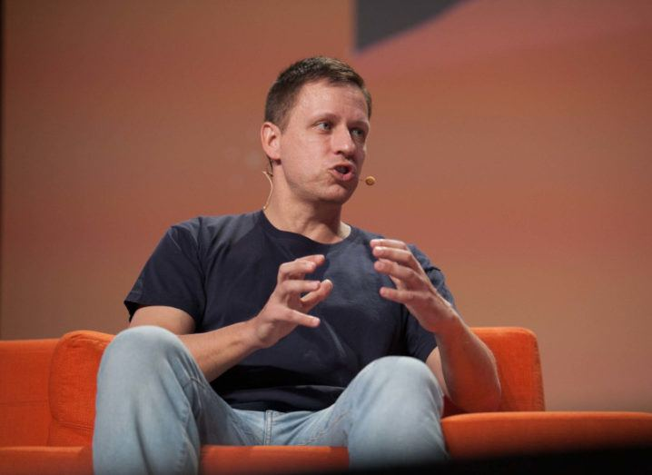 Peter Thiel sits on an orange chair amid an on-stage discussion. He is wearing a head mic.