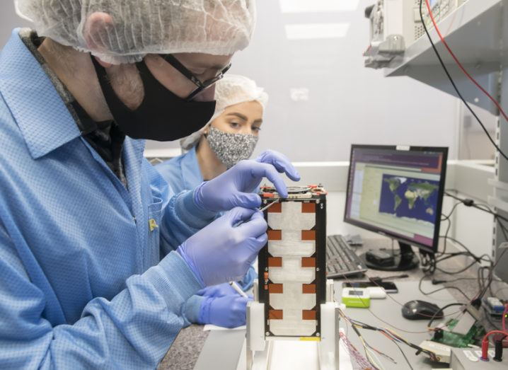 Two researchers in protective equipment are working on satellite tech in a lab.